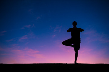 Silhouette of man balancing on one leg in a standing yoga tree pose in front of bright colorful sunrise sky
