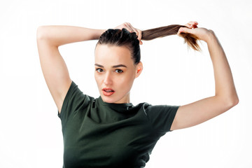Portrait of young girl adjusts her hair in a ponytail in studio. Youth, tender age and lifestyle concept. Fashionable young woman tying her beautiful ginger hair in ponytail.