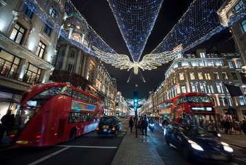 Busy holiday shopping scene with double decker buses and black cabs zooming past pedestrians on a winter night on Regent Street, London