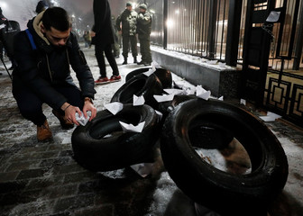 A man places a paper boat during a protest against the seizure by Russian special forces of three of the Ukrainian navy ships in the Black Sea, in front of the Russian embassy in Kiev
