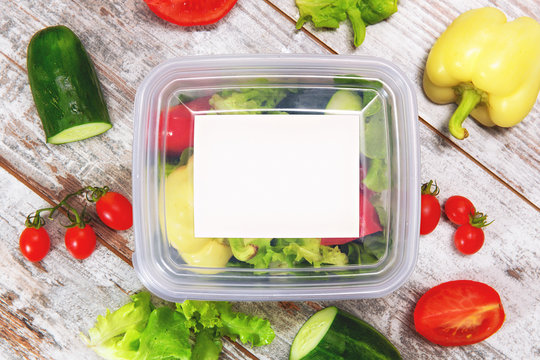 Organic salad inside plastic package. Fresh veggies on top of the wooden table.