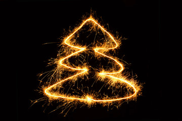 Christmas tree drawing sparkling sparklers on black background