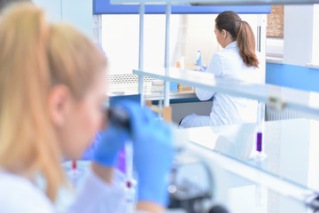 Two Young Female Laboratory scientist working at lab with test tubes, test or research in clinical laboratory.Science, chemistry, biology, medicine and people concept.
