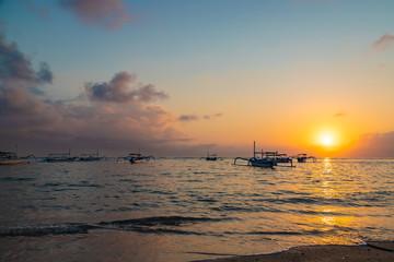 Beautiful sunrise at Sanur Beach, Bali. Traditional fishing boat on seashore at colorful sunrise. Indonesia.