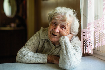 Portrait of elderly pensioner lady sitting at the table. Fototapete