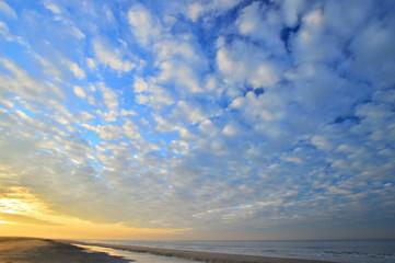 Nadmorskie wybrzeże, plaża i morze pod niebieskim niebem z chmurami.