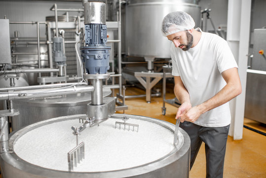 Man mixing milk in the stainless tank during the fermentation process at the cheese manufacturing