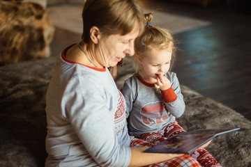Grandma and granddaughter have fun together reading a book on the bed . Family Christmas concept. Selective focus.