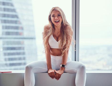 Beautiful fitness model sitting on a window sill in a skyscraper apartment.
