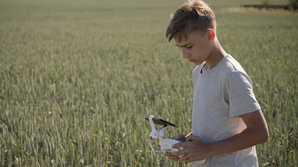 Young boy teenager flying a modern drone control on a sunny day in a wide open wheat field technologically advanced