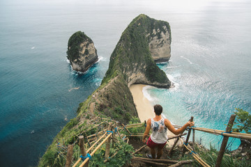 Foto op Aluminium Bali Adventurous man standing on top of Kelingking beach and unique rock formations on Nusa Penida, Indonesia.