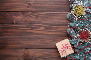 Snowflakes and gift on a brown wooden background.