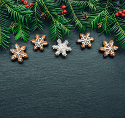 Frame with fir branches, Gingerbread cookies and Christmas decorations on dark wooden background. Top view.