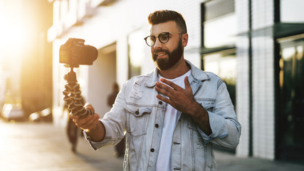 Bearded male hipster blogger in trendy glasses standing on city street, holds camera on tripod and shoots video blog.