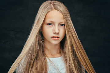Portrait of a beautiful young girl with blonde hair looking at a camera