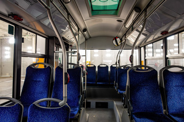 Interior of a modern city bus with blue seats