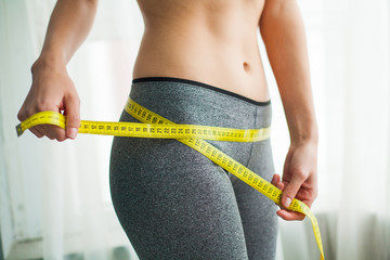 Hands measuring waist with a tape. Slim and healthy woman at her home