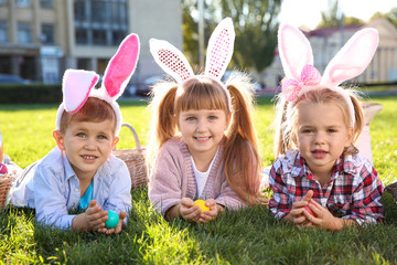 Cute little children with bunny ears and Easter eggs in park