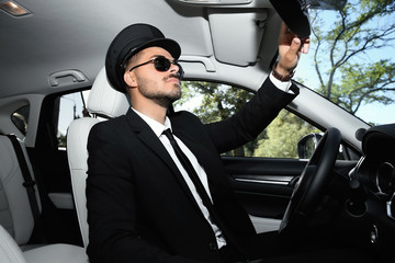 Young handsome driver adjusting interior mirror in luxury car