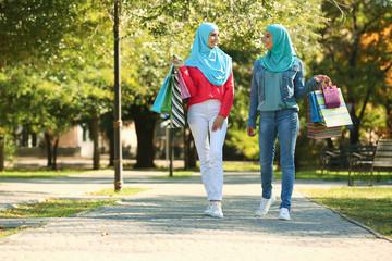 Muslim women with shopping bags walking in park