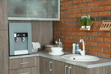 Kitchen counter with water cooler, sink and clean dishes, indoors