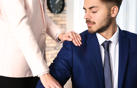 Woman molesting her male colleague in office, closeup. Sexual harassment at work