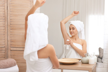 Beautiful young woman applying deodorant after shower in bathroom