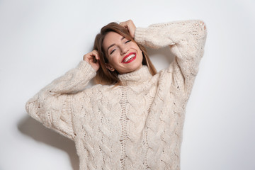 Wall Mural - Beautiful young woman in warm sweater on white background