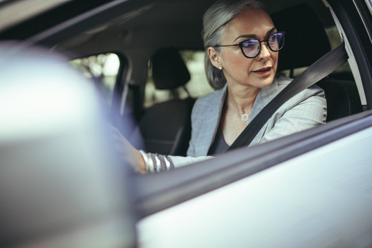 Senior woman driving a car in the city