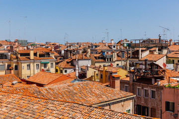 Terracotta rooftops of venetian houses under blue sky in Venice, Italy