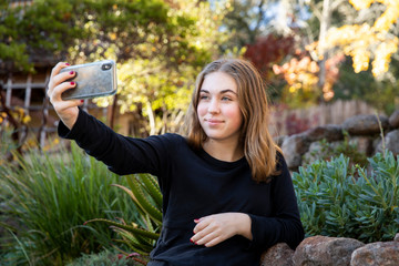 Teenage girl taking a selfie with a smart phone outdoors