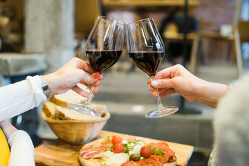 woman hands toasting with glasses of red wine