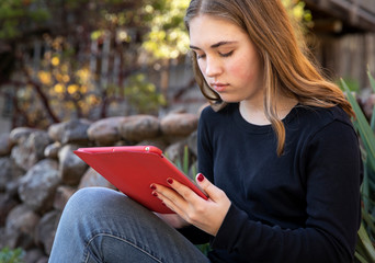 Teenage girl holding a tablet outdoors