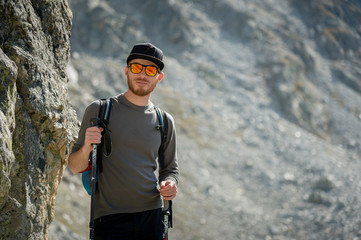 Porter of a stylish hipster traveler with a beard and a backpack in sunglasses and a cap with trekking poles stands on a rock against the backdrop of a mountain circus