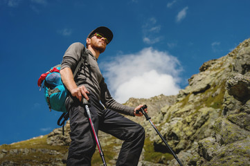 Porter of a stylish hipster traveler with a beard and a backpack in sunglasses and a cap with trekking poles standing on a rock against the background of a slope and blue sky in the mountains