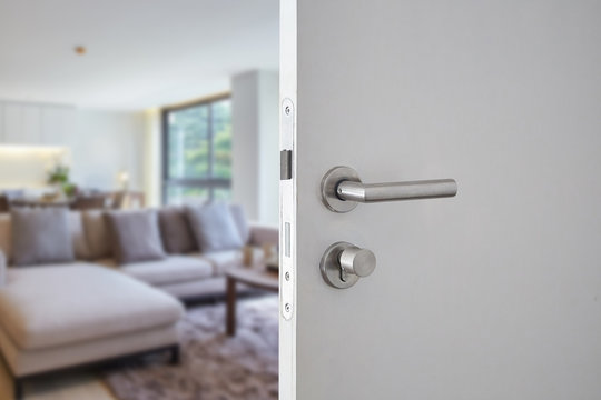Door handle ,hotel or apartment door open in front of blur living interior room background, selective focus