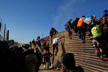 Migrants climb the border fence between Mexico and the United States in an attempt to cross into the U.S side of the border in Tijuana, Mexico