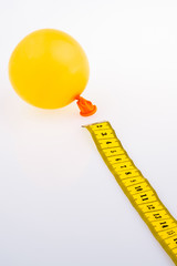 Yellow color measuring tape and a baloon