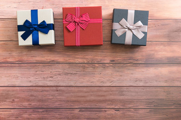 Gift boxes with ribbon on wooden table, copy space. Gifts and celebration, holydays and christmas background
