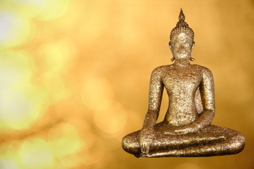 Golden Buddha statue on golden abstract background