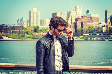 European businessman traveling on East River in New York. Wearing leather jacket, sunglasses, young guy with beard, looking down, sad, thinking, missing family, friends, home. Brooklyn on background.