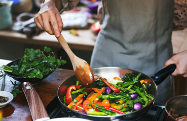 Foto auf Acrylglas Kochen Woman cooking stir fried vegetables