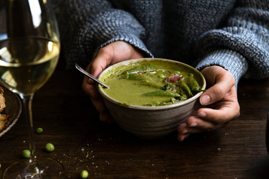 Woman holding a bowl of green pea soup