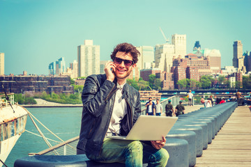 Businessman enjoying working on site. Wearing leather jacket, sunglasses, a guy with beard, sitting on bench at harbor, working on laptop computer, talking on phone in the same time. Filtered effect.