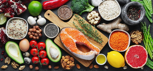 Healthy food clean eating selection: fish, fruit, nuts, vegetable, seeds, superfood, cereals, leaf vegetable on black concrete background. Flat lay