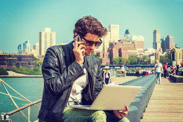 Businessman traveling, working in New York. Wearing sunglasses, a young guy with beard, sitting on bench at harbor, working on laptop computer, talking on phone in the same time. Filtered effect.