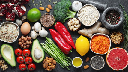 Healthy food clean eating selection: fruit, vegetable, seeds, superfood, cereal, leaf vegetable on black concrete background. Flat lay