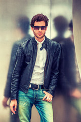 Man Spring/Autumn Casual Fashion. Young guy with beard, wearing black leather jacket unbuttoned, blue jeans, sunglasses, leaning against silver metal wall, smoking cigarette, relaxing, thinking.
