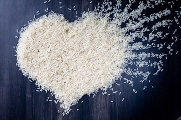 top view heart symbol of parboiled rice on black background