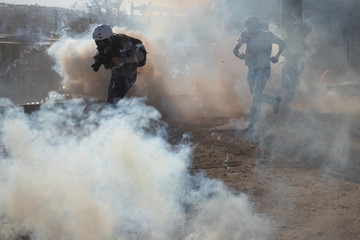 Photographer Kim Kyung-Hoon works through tear gas tear fired on migrants trying to illegally cross the Mexico border into U.S. from Tijuana, Mexico